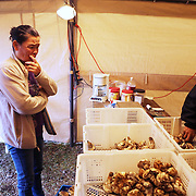 Som Piada, left, sells mushrooms to Soulinh Souvannasay in the parking lot of the Crater Lake Inn in Chemult, Ore. A day of picking netted Piada $87.29 worth of matsutakes, which Souvannasay rounded up to $90.00. The elusive matsusake mushroom, which fetches a pretty penny in Japanese restaurants, can begin its journey on the floor of the Fremont-Winema National Forest in Chemult, Ore. Here immigrants from Laos, Cambodia and other countries search for the mushrooms, creating a fungal economy and an ad hoc community.