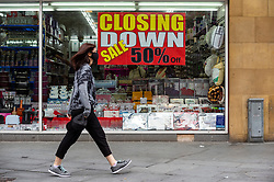 © Licensed to London News Pictures. 20/08/2021. LONDON, UK.  A woman walks past a store closing down sign in the town centre of Harrow-on-the-Hill, north-west London.  The Office for National Statistics (ONS) has announced that UK retail sales dropped in July to their lowest level since shops reopened in April with retailers reporting that Euro 2020 football tournament and bad weather kept shoppers away from stores.  Photo credit: Stephen Chung/LNP