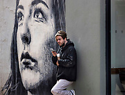 Phone call and morning coffee in front of a wall mural on 21st April 2021 in Blackpool, Lancashire, United Kingdom. Blackpool is a large town and seaside resort in the county of Lancashire on the north west coast of England. Blackpool was once a booming resort with it's famous promenade which now, despite having a somewhat shabby appearance, still continues to attract millions of visitors each year. During the coronavirus pandemic however, Blackpool has struggled, with empty streets and closed down businesses creating an atmosphere more like a ghost town.