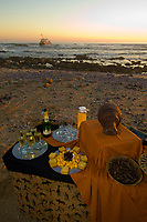 A Sundowner (cocktail party) on  the Skeleton Coast at sunset (a shipwreck, the  Kilmanskop in background), Swakopmund, (the Atlantic Ocean off of the Namib Desert coastline), Namibia