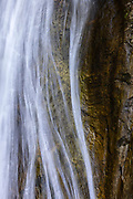 Strands of falling water curve around the rocky backdrop of Lower Twin Falls, a 135-foot (41-meter) waterfall in Olallie State Park near North Bend, Washington.