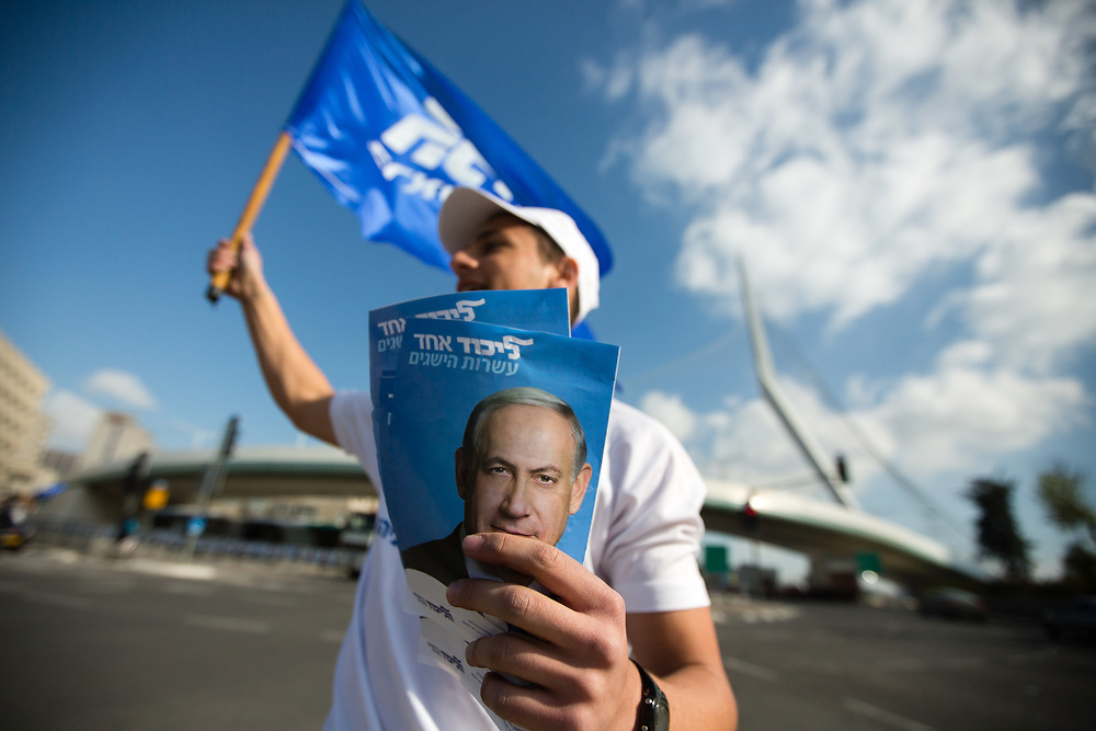 A supporter of the right-wing Likud party hands out fliers with the picture of Israel's Prime Minister Benjamin Netanyahu, as he campaigns in Jerusalem, Israel, on March 15, 2015, two days ahead of legislative elections in Israel.