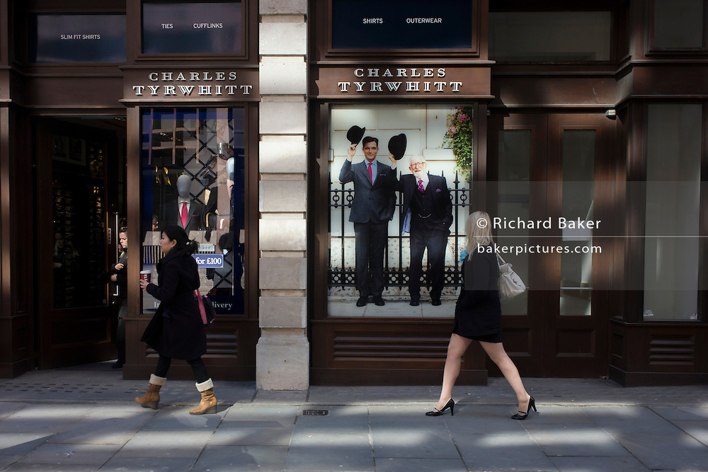 Two women walk past the Charles Tyrwhitt menswear outfitters in Eldon Street in the City of London, the capital's heart of its financial district and a good location for suits and businesswear. A pair of Englishmen raise their bowler hats in a gesture from a previous era, when hats said much of your social standing, a summary of your position in the class system. In the 21st century though, the hat is largely an item of clothing to wear only for extreme cold or heat. A leggy girl strides past the shop frontage, seemingly curious of this bygone gentlemanly tradition.