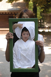 Japanese bride in traditional marriage costume reflected in mirror at Meiji Shrine in Tokyo Japan