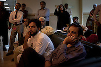 People react while watching a television interview showing Imran Khan, chairman of the Pakistan Tehreek-e-Insaf political party, in the foyer of the Shaukat Khanum Memorial Cancer Hospital and Research Centre in Lahore, Pakistan, Tuesday, May 7, 2013. Khan was injured falling from a forklift truck while arriving on stage at a campaign rally in Lahore.