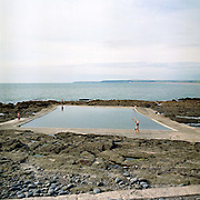 A group of young people play games on the edge of The Rock Pool, Westward Ho!, Devon, UK. Located at the southern end of Westward Ho! beach near Bideford, this renovated pool has been here for 120 years. Until the 1950s and the rise of the heated indoor swimming pool, children learnt to swim outdoors. For those close to the sea, many man-made tidal swimming pools were constructed around Britain's coastline. Heated by the sun, these tidal pools were often built to keep bathers safe from high and rough seas, which explains why so many of them are clustered in Scotland and around the surfing beaches of Cornwall. Whether they are simple swimming holes made by shoring up natural rock pools or grand lido-like pools complete with lifeguards and tea huts, they are all refreshed by good high tides.