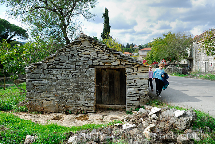 Two children (9 years old, 5 years old) walking beside traditional stone building in village of Zrnovo, island of Korcula, Croatia