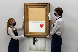 """© Licensed to London News Pictures. 03/09/2021. LONDON, UK.  **UNDER EMBARGO UNTIL FRIDAY 3 SEPTEMBER 2021, 12PM BST** Technicians present """"Love Is in the Bin"""" by Banksy at a preview at Sotheby's.  The painting, originally known as """"Girl with Balloon"""", was famously shredded by the artist in Sotheby's London auction room in 2018 after being sold for £1,042,000.  The resulting artwork was later renamed """"Love Is in the Bin"""" and will be offered for sale in Sotheby's contemporary art evening auction on October 14 with an estimate of £4-6 million.  Photo credit: Stephen Chung/LNP"""