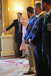 Queen Elizabeth II joins the captains of the teams taking part in the ICC Cricket World Cup for a photograph in the 1844 Room at Buckingham Palace in London, ahead of the competition's Opening Party on the Mall.