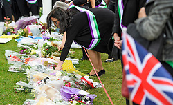 © Licensed to London News Pictures. 22/06/2016. London, UK. Representatives from NGO's place flowers outside the Houses of Parliament in London, ahead of a memorial service to mark the life of the Labour MP for Batley and Spen, Jo Cox, who was murdered near her constituency office.  Jo Cox would have turned 42 today. Photo credit: Ben Cawthra/LNP