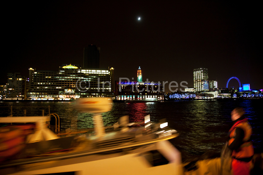 Boat on the River Thames passes on the opposite side from the Oxo Tower at night. With the moon glowing directly above this famous London landmark on the South London skyline on the Southbank.
