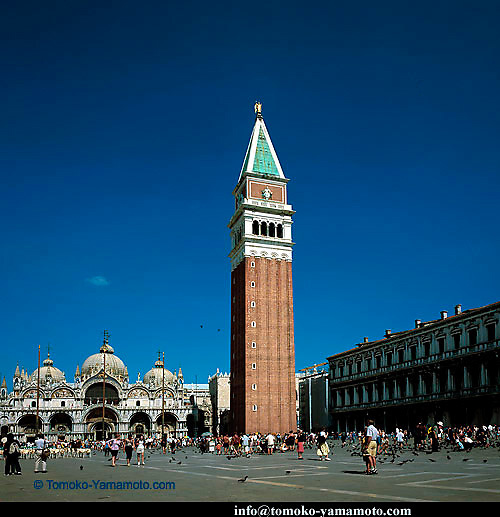 A square of Piazza San Marco which shows the Campanile in the center and the Basilica to the left and the arcaded façade of Procuratie Nuove on the south side.  Tourists and pigeons.  The sky has a patch of clouds above the main dome of the Basilica.