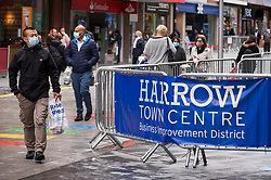 © Licensed to London News Pictures. 12/10/2020. LONDON, UK. Shoppers wearing facemasks pass through in Harrow town centre.  It is reported that five London boroughs had more than 100 new COVID-19 cases per 100,000 population in the week to October 8 — Richmond, Hackney, Ealing, Redbridge and Harrow.  As the UK experiences a rise in the number COVID-19 cases nationwide, Boris Johnson, Prime Minister is announcing in the House of Commons a new three-tier local lockdown system to tackle the spread of the virus.  Photo credit: Stephen Chung/LNP
