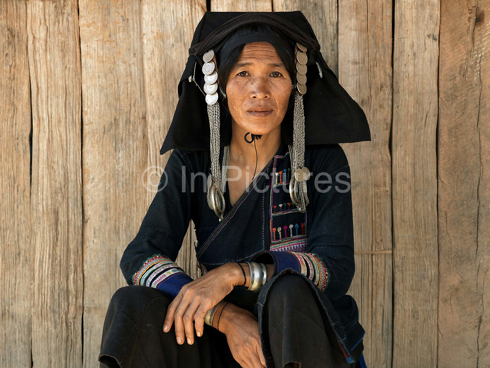 Che Le, an Akha Puxo ethnic minority woman sits outside her wooden home in Ban Nam Yang village, Phongsaly Province, Lao PDR. One of the most ethnically diverse countries in Southeast Asia, Laos has 49 officially recognised ethnic groups although there are many more self-identified and sub groups. These groups are distinguished by their own customs, beliefs and rituals. Details down to the embroidery on a shirt, the colour of the trim and the type of skirt all help signify the wearer's ethnic and clan affiliations.