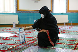 "© Licensed to London News Pictures. 06/07/2020. London, UK. Mrs Bibi Khan, president of London Islamic Cultural Society and Mosque wearing face covering places a ""PRAY HERE' sign as worshippers will be 2 meters apart. Wightman Road Mosque, also known as London Islamic Cultural Society and Mosque, in north London, prepares to open after the COVID-19 lockdown, by placing a number of measures required by law for worshippers. The government announced that gatherings of more than 30 worshippers are allowed for acts of communal worship in churches, synagogues, mosques, temples and other places of worship. All worshippers attending Mosques will have to wear face coverings and bring their own prayer mat, Quran, and a reusable shoe bag. Photo credit: Dinendra Haria/LNP"