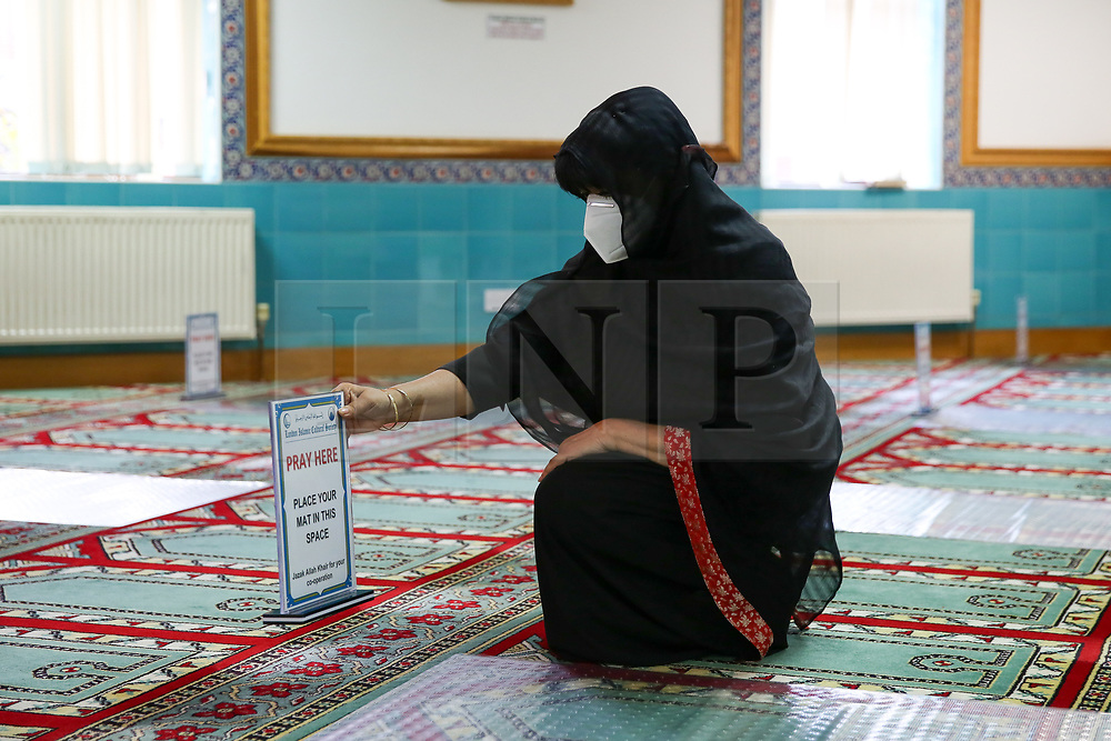 """© Licensed to London News Pictures. 06/07/2020. London, UK. Mrs Bibi Khan, president of London Islamic Cultural Society and Mosque wearing face covering places a """"PRAY HERE' sign as worshippers will be 2 meters apart. Wightman Road Mosque, also known as London Islamic Cultural Society and Mosque, in north London, prepares to open after the COVID-19 lockdown, by placing a number of measures required by law for worshippers. The government announced that gatherings of more than 30 worshippers are allowed for acts of communal worship in churches, synagogues, mosques, temples and other places of worship. All worshippers attending Mosques will have to wear face coverings and bring their own prayer mat, Quran, and a reusable shoe bag. Photo credit: Dinendra Haria/LNP"""
