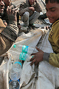 A youngster counts his bottles getting into an argument with one of his fellow raiders as to whos bottles they are.  Children, some who have run away from their families, find themselves living homeless on the train tracks waititng for the next train to arrive at the train station in Jaipur, India.  Once the train arrives they raid the train looking for plastic bottles that they can then sell.  Most will make about $1.50/day but spend most of it on glue which they are most addicted to.