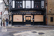 Two men walk past the Coach and Horses Pub on Bruton Lane in Mayfair that is all boarded up for Lockdown 3 on the 26th of January 2021, London, United Kingdom. Many shops and pubs in central London boarded up their windows for security purpose when they were told they would be shut for a number of months due to another COVID-19 lockdown.