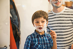 Son shaving in bathroom while father watches, Munich, Germany