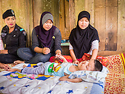 17 JUNE 2015 - RANGAE, NARATHIWAT, THAILAND:  Thai Army Ranger 2nd Lt MONTHA SOMPIASERT, left, and a medic from her unit talk to a Thai Muslim woman in her home. Her son was born with birth defects. The Rangers bring them food and perform wellness checks as a part of the Rangers' outreach program. There are 5 platoons of women Rangers serving in Thailand's restive Deep South. They generally perform security missions at large public events and do public outreach missions, like home wellness checks and delivering food and medicine into rural communities. The medics frequently work in civilian clothes because the Rangers found people are more relaxed around them when they're in civilian clothes. About 6,000 people have been killed in sectarian violence in Thailand's three southern provinces of Narathiwat, Pattani and Yala since a Muslim insurgency started in 2004. Attacks usually spike during religious holidays. Insurgents are fighting for more autonomy from the central government in Bangkok.    PHOTO BY JACK KURTZ