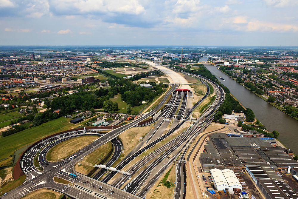 Nederland, Utrecht, Leidsche Rijn, 13-05-20011; zuidelijke ingang van de nieuwe landtunnel voor de A2, verkeersplein Hooggelegen onder in beeld. De tunnel ligt parallel aan de bestaande A2, het asfalt zal op termijn verdwijnen en op het dak van de tunnel zal een park komen. Links van de tunnel Leidsche Rijn met de wijken Langerak en Parkwijk. Rechts het Amsterdam-Rijnkanaal. Southern entrance of the new landtunnel for A2. The tunnel lies parallel to the existing motorway A2, the asphalt will eventually disappear and the roof of the tunnel will be a park. Left of the tunnel Leidsche Rijn with the districts and Langerak Parkwijk. Right the Amsterdam-Rhine Canal..luchtfoto (toeslag), aerial photo (additional fee required).foto/photo Siebe Swart