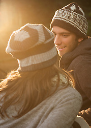 Smiling young man facing young woman