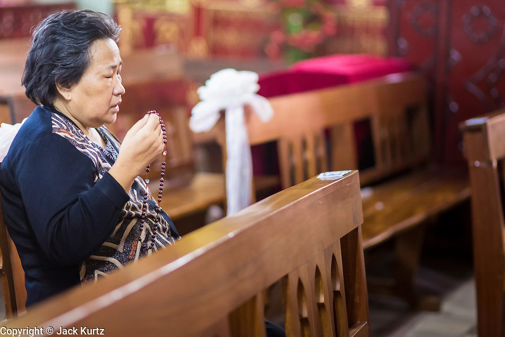 08 APRIL 2012 - HANOI, VIETNAM:     A woman prays in the Cathedral on Easter Sunday in St. Joseph Cathedral in Hanoi, Vietnam. St. Joseph Cathedral in Hanoi is the seat of the Roman Catholic Archdiocese of Hanoi and is one of the most important Catholic churches in Vietnam. It was built in 1886 and is especially crowded on religious holidays, like Easter. The church holds three Easter masses on Easter Sunday morning. There are more than 5.6 million Roman Catholics in Vietnam, nearly 7% of the population. Catholicism came to what is now Vietnam with Portuguese missionaries in the 16th Century, but it wasn't until the arrival of French missionaries and later colonial authorities that Catholicism became a part of Vietnamese religious life.   PHOTO BY JACK KURTZ