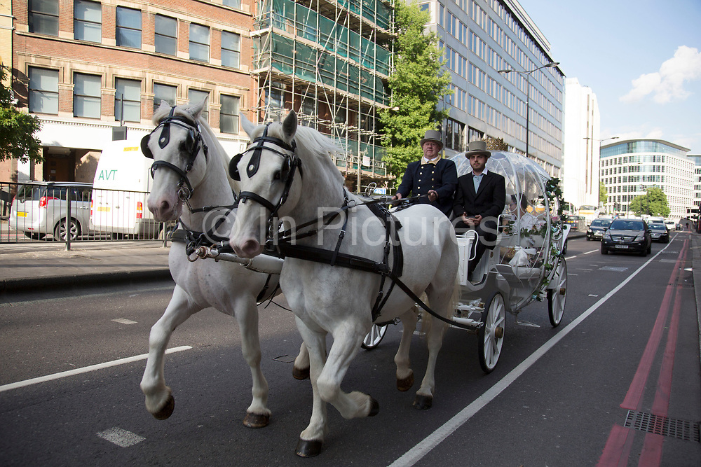 Chinese wedding couple in a horse drawn Cinderella carriage on Lower Thames Street in London, UK. It is a common site now to see extravagant and visual elements to Asian weddings in the UK. Two white blinkered horses, a driver and a footman is an extreme version of this.