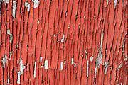 Old red paint peeling from a weathered exterior wall.