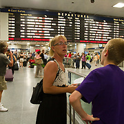 Travelers wait for train track announcement at Penn Station in New York.