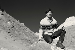 Asian American man kneeling down on a rock formation in New Mexico