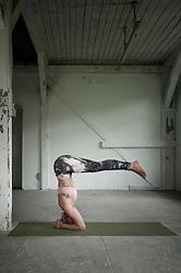 Mid adult woman practicing headstand pose in yoga studio, Munich, Bavaria, Germany