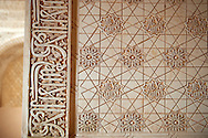 """Moorish architectural sculpted plasterwork of the Palacios Nazaries, Alhambra. Granada, Andalusia, Spain. . The Alhambra is a palace and fortress complex located in Granada, Andalusia, Spain. It was originally constructed as a small fortress in 889 CE on the remains of ancient Roman fortifications. The Alhambra was renovated and rebuilt in the mid-13th century by the Arab Nasrid emir Mohammed ben Al-Ahmar of the Emirate of Granada, who built its current Alhambra palace and walls. The Alhambra was converted into a royal palace in 1333 by Yusuf I, Sultan of Granada. The decoration of The Alhambra consists for the upper part of the walls, as a rule, of Arabic inscriptions—mostly poems by Ibn Zamrak and others praising the palace—that are manipulated into geometrical patterns with vegetal background set onto an arabesque setting (""""Ataurique""""). Much of this ornament is carved stucco (plaster) rather than stone. Tile mosaics (""""alicatado"""") of The Alhambra, with complicated mathematical patterns (""""tracería"""", most precisely """"lacería""""), are largely used as panelling for the lower part. .<br /> <br /> Visit our SPAIN HISTORIC PLACXES PHOTO COLLECTIONS for more photos to download or buy as wall art prints https://funkystock.photoshelter.com/gallery-collection/Pictures-Images-of-Spain-Spanish-Historical-Archaeology-Sites-Museum-Antiquities/C0000EUVhLC3Nbgw <br /> .<br /> Visit our ISLAMIC HISTORICAL PLACES PHOTO COLLECTIONS for more photos to download or buy as wall art prints https://funkystock.photoshelter.com/gallery-collection/Islam-Islamic-Historic-Places-Architecture-Pictures-Images-of/C0000n7SGOHt9XWI"""