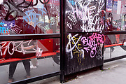Graffiti covers a bus shelter on the Walworth Road at Elephant & Castle, Southwark,  on 27th May 2021, in London, England.