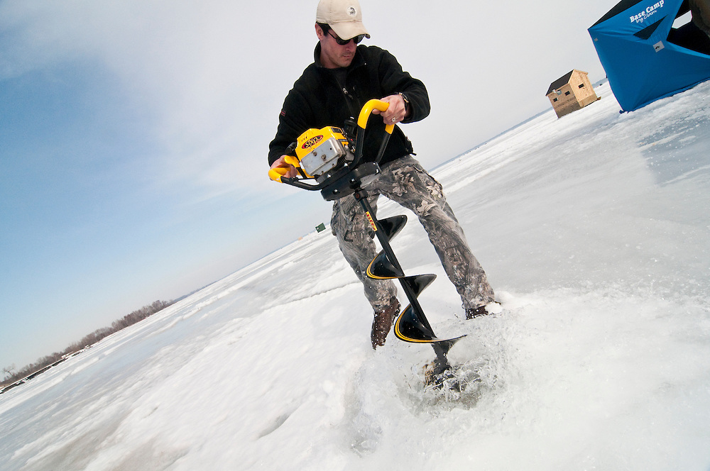 An ice fisherman uses a power auger to bore holes for fishing on Little Bay de Noc near Gladstone and Escanaba Michigan.