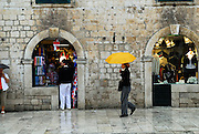 """A woman with a yellow umbrella walks past unique """"na koljeno"""" style of door/window/counter--traditionally the door was closed and the horizontal surface became the counter over which trade was conducted. Dubrovnik old town, Croatia"""