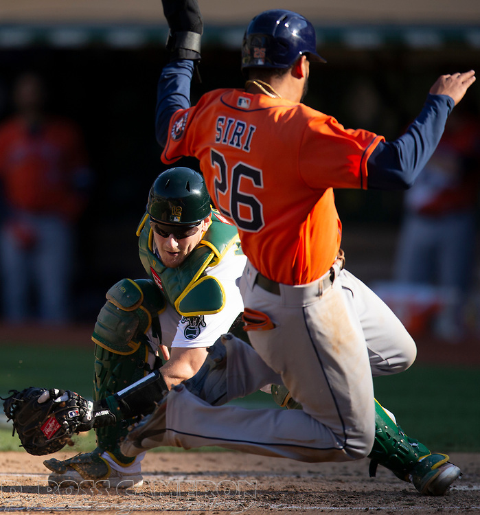 Sep 26, 2021; Oakland, California, USA; Oakland Athletics catcher Sean Murphy (12) prepares to put the tag on Houston Astros center fielder Jose Siri (26) as he tries to score on Alex Bregman's single in the ninth inning at RingCentral Coliseum. Mandatory Credit: D. Ross Cameron-USA TODAY Sports