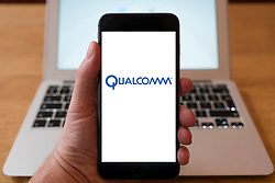 Using iPhone smartphone to display logo of Qualcomm, multinational semiconductor and telecommunications equipment company