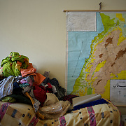 Belongings from a family of Syrian refugees, standing beside the map of Lebanon and Syria displayed in a wall at an improvised room at Wadi Khaled' refugee center in Lebanon.
