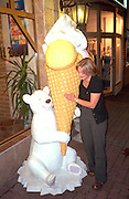 Woman age 20 speaking to statue of bear with ice cream cone.  Gniesno Poland