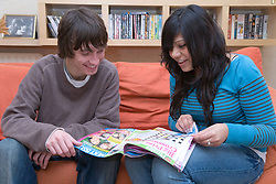 Teenagers reading a magazine together,