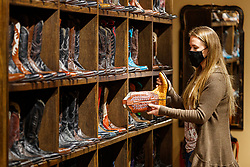 Salesperson checking boots on display in historic M.L Leddy's Boots, Fort Worth Stockyards National Historic District, Fort Worth, Texas, USA.