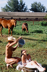 naked cowboy pouring a bucket of water over a girl taking an outdoor bubble bath on a horse ranch in New Mexico