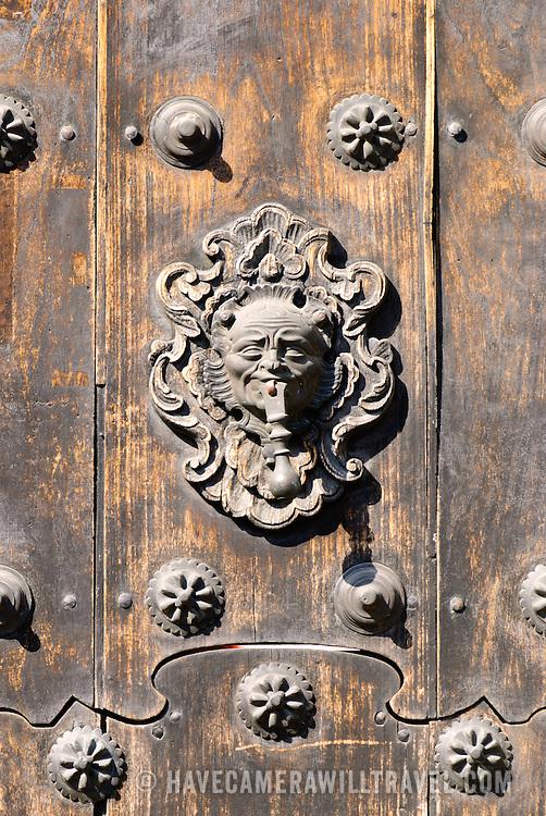 An ornate door knocker on a heavy wooden door at Iglesia de San Francisco in Antigua, Guatemala.