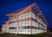 large office exterior at dusk with lights on