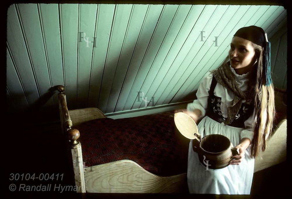Signy Kjartansdottir, a costumed guide at Arbaer Folk Museum, sits on bed w/ carved wood bowl. Iceland