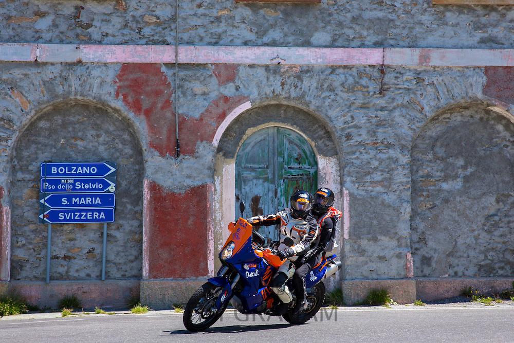 Motorcyclist and passenger on KTM Dakar motorbike on The Stelvio Pass, Passo dello Stelvio, Stilfser Joch, to Bormio, Italy