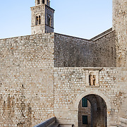 """An interior wall and the Ploce Gate in the old city of Dubrovnik, Croatia. The bell tower of the Dominican Church can be seen in the background. Above the Ploce Gate stands a stone statue of St. Blaise, the City's patron.<br /> <br /> Dubrovnik serves as the official setting of """"King's Landing"""" from the popular TV show """"Game of Thrones""""."""