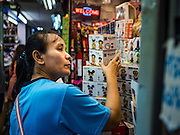 11 OCTOBER 2015 - BANGKOK, THAILAND: A woman shops for toys on what Bangkok city government is calling the last day for business in Saphan Lek market. Many shops in the market are already closed. Street vendors and illegal market vendors in the Saphan Lek area will be removed in the next two weeks as a part of an urban renewal project coordinated by the Bangkok Metropolitan Administration. About 500 vendors along Damrongsathit Bridge, popularly known as Saphan Lek, have until Monday, October 11,  to relocate. Vendors who don't move will be evicted. Saphan Lek is one of several markets and street vending areas being closed in Bangkok this year. The market is known for toy and replica guns, bootleg and pirated DVDs and CDs and electronic toys.    PHOTO BY JACK KURTZ