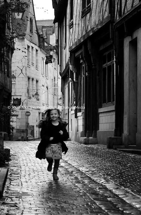 Girl running through the streets of Chinon in France.